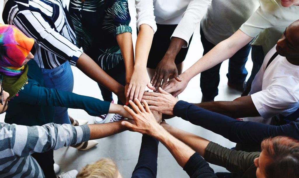 Diverse group of people putting hands in a circle